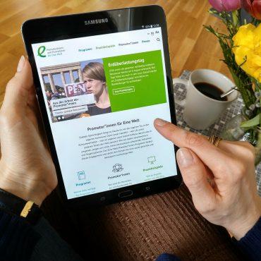 Eine Frau tippt auf einem Tablet und schaut sich die Webseite des Eine Welt-Promotoren-Programms an